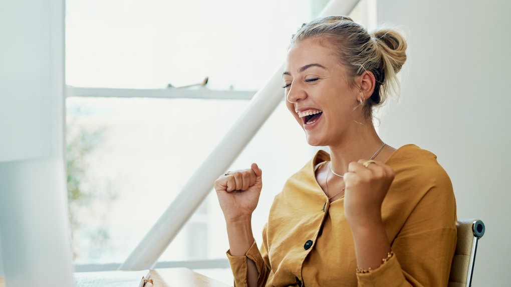 A young woman cheers while sitting at her kitchen table on a spring day and video chatting on her laptop.