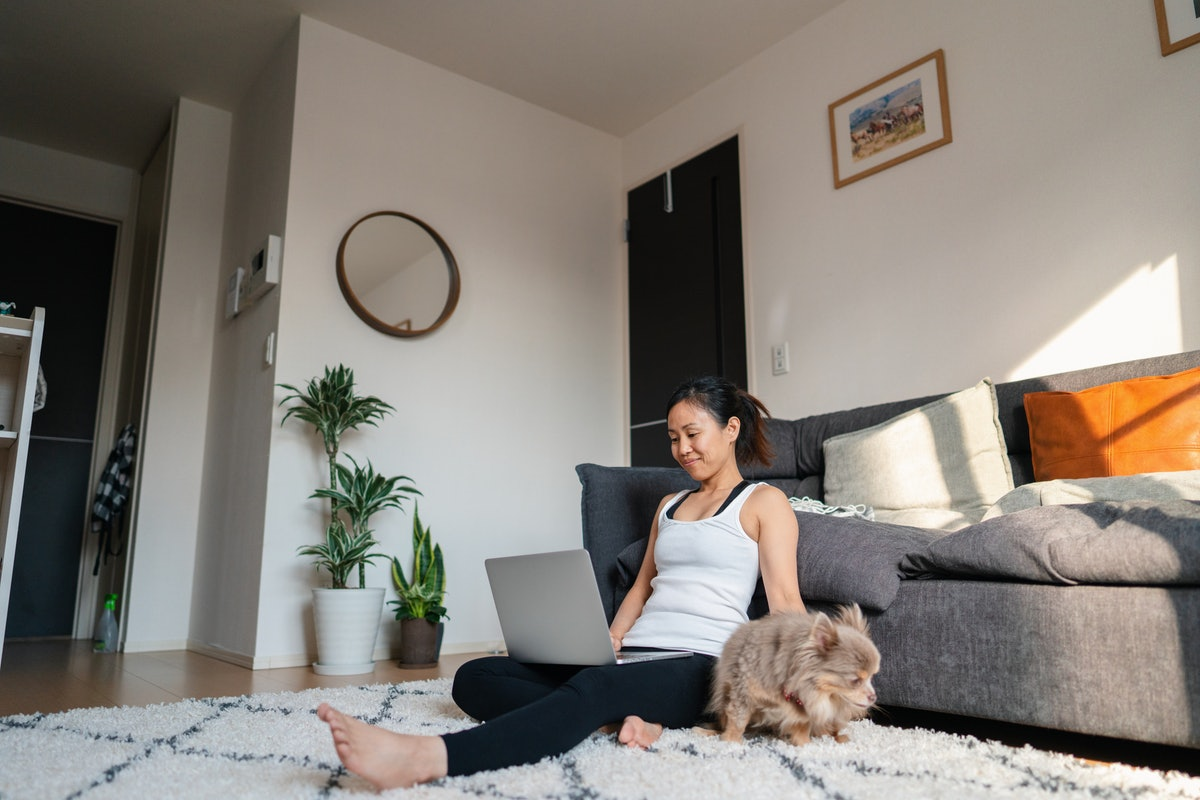 A young woman sits on her living room floor with her dog and video chats on her laptop.