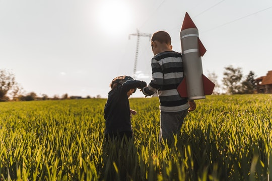 two brothers walking through tall grass with a rocket