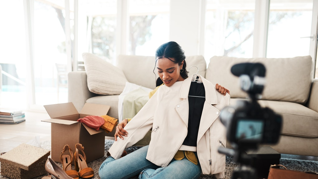 A young woman sits on her living room floor and unboxes new clothes while recording herself on a digital camera.