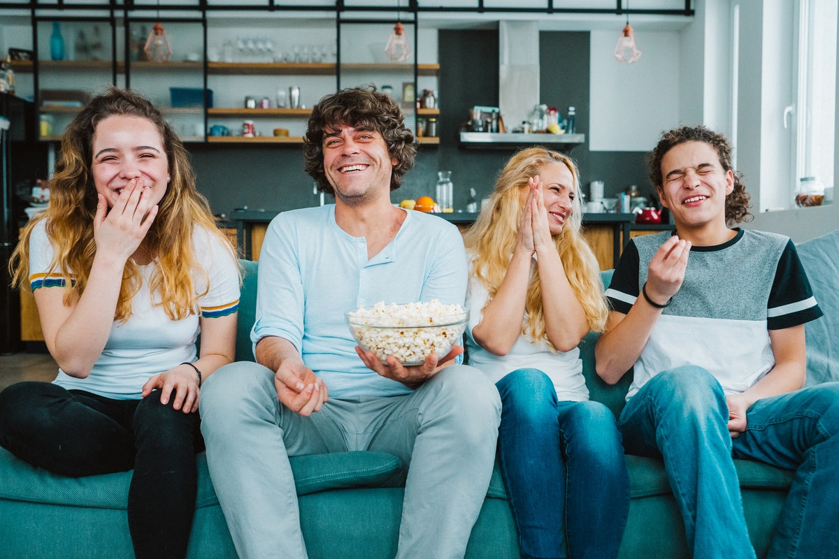 A family sits on a teal couch in their home and laughs while watching a movie and eating popcorn.