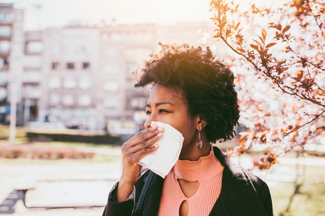 A woman covers her face around blossom. Allergens can trigger asthma attacks.