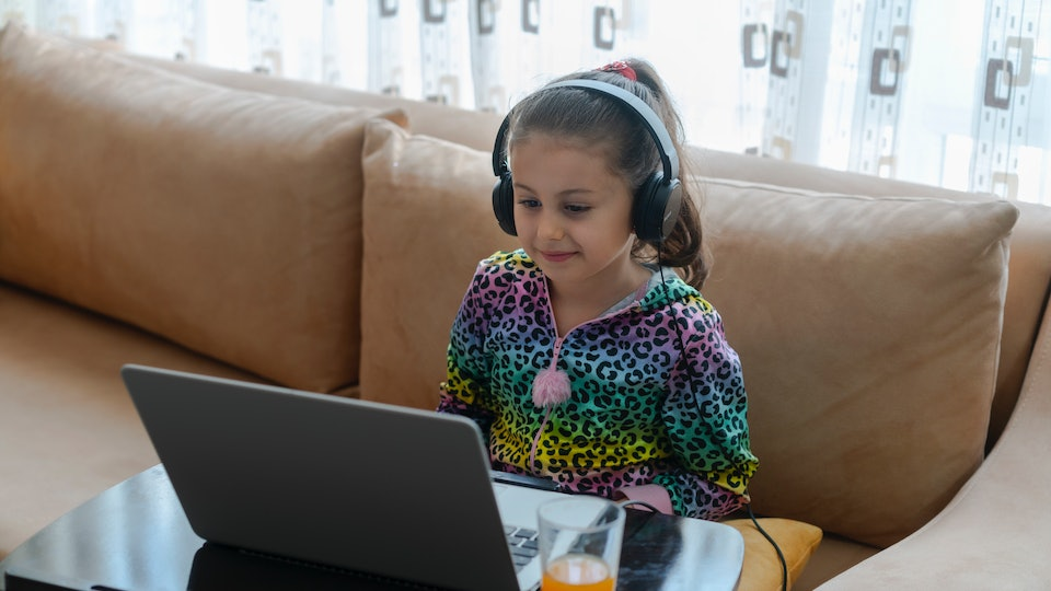 girl sitting on couch wearing headphones in front of laptop