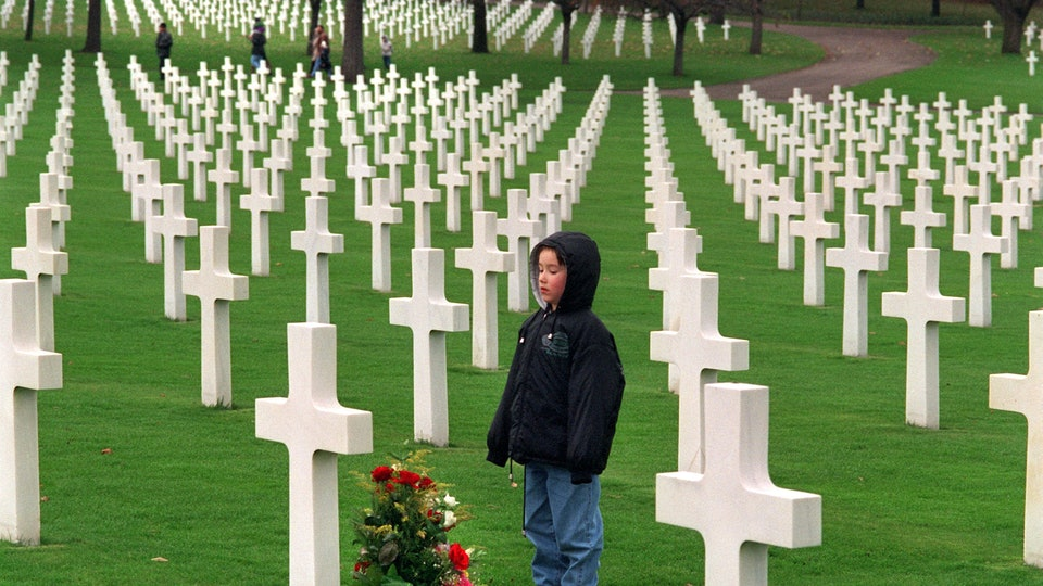 kid standing at a grave in a military cemetery