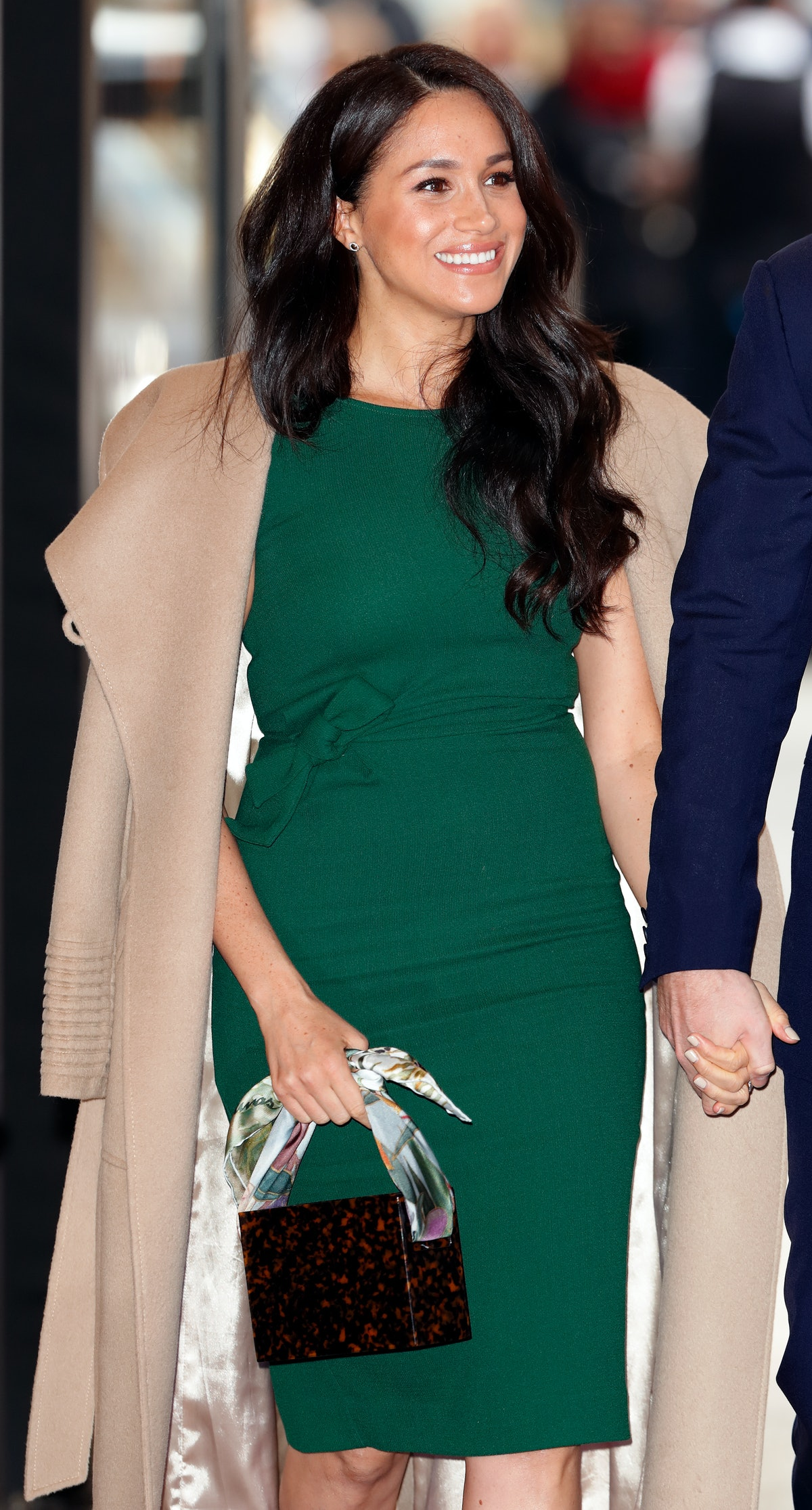 Meghan Markle wore a wool coat over an emerald fitted dress for the WellChild Awards in October 2019...