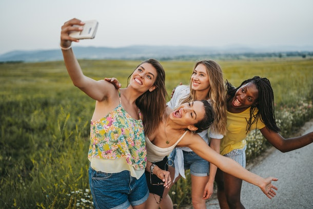 Four young women take a funny selfie while standing next to a grassy field.