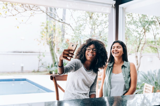 Two young women smile while sitting on an outdoor patio and taking a selfie.