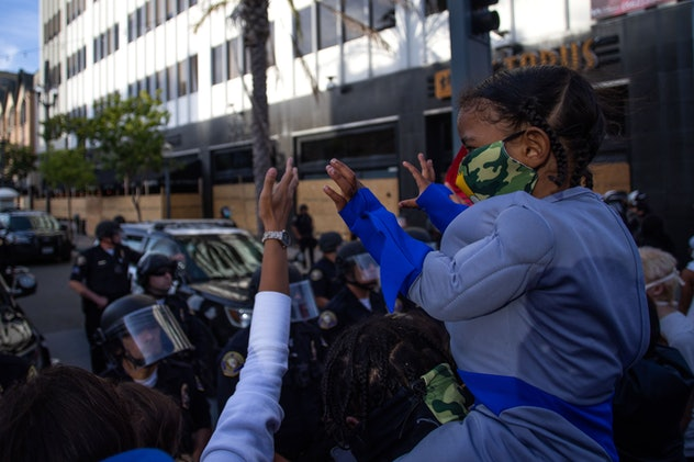 A boy holds his hands up in front of the police