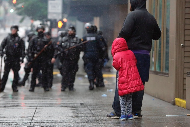 A childl hides behind an adult in front of a line of police