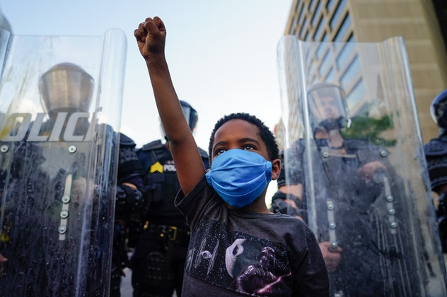 A young boy holds his fist high at a protest