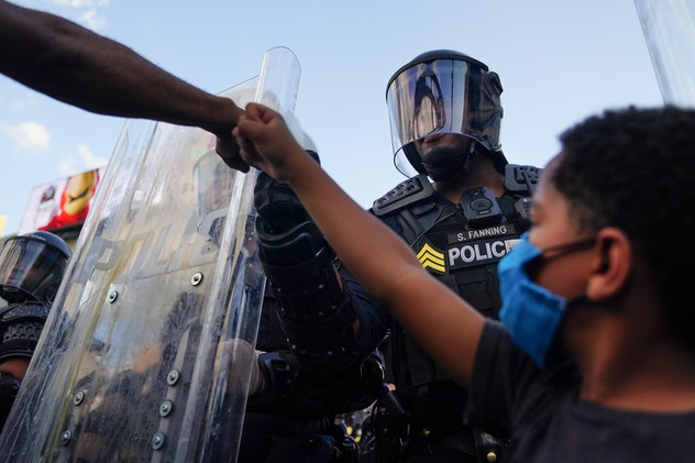 Protestors and police officer fist bump