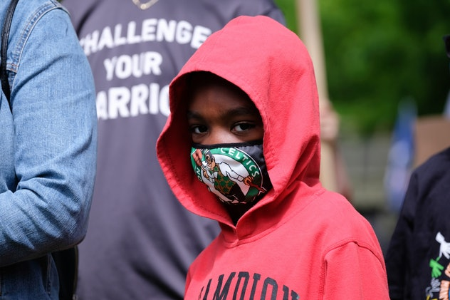 A young boy wears a mask while protesting