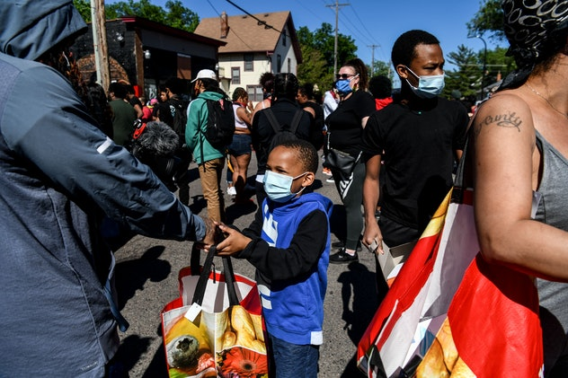 A young boy distributes food and water to protestors