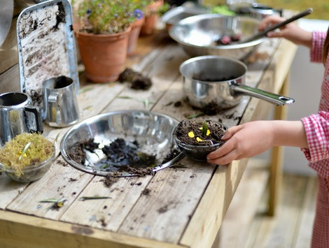 girl playing in mud kitchen