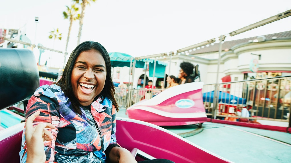 A young Black woman laughs while riding in a hot pink cart at an amusement park in the summertime.