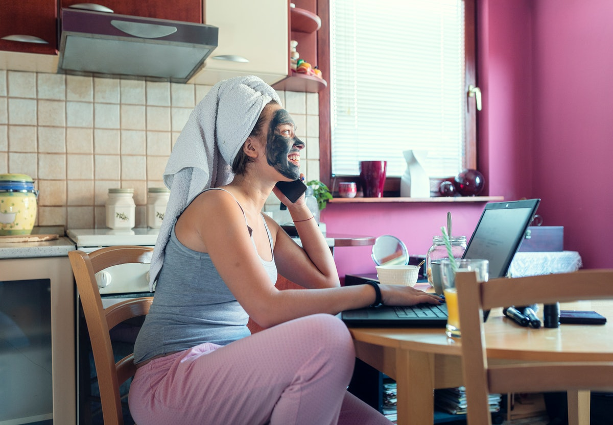 A young woman sits at her kitchen table and talks on the phone while doing a facial and wearing her hair in a towel.