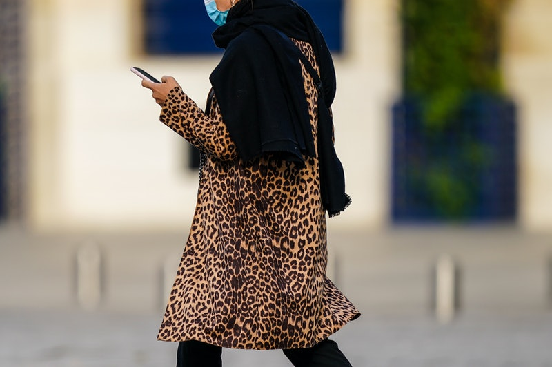 A woman in a headscarf and leopard print wears a facemask. How To Talk To Somebody Who Refuses To Wear A Face Mask, According To Experts