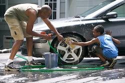 black dad and son washing car