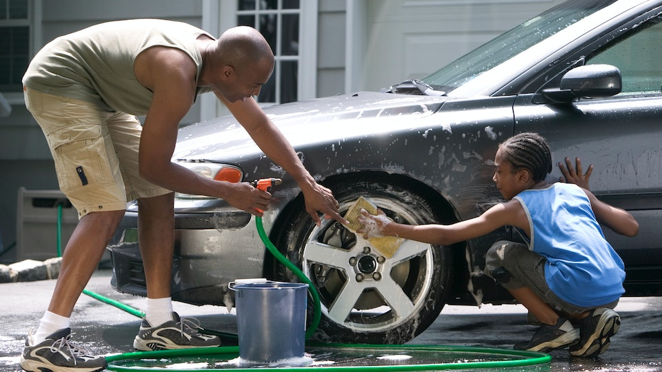 black dad and son washing car