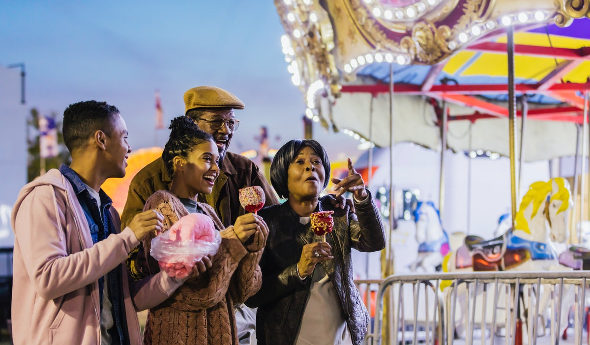 A Black family goes to a carnival at night and eats cotton candy and candy apples near a merry-'go-round.
