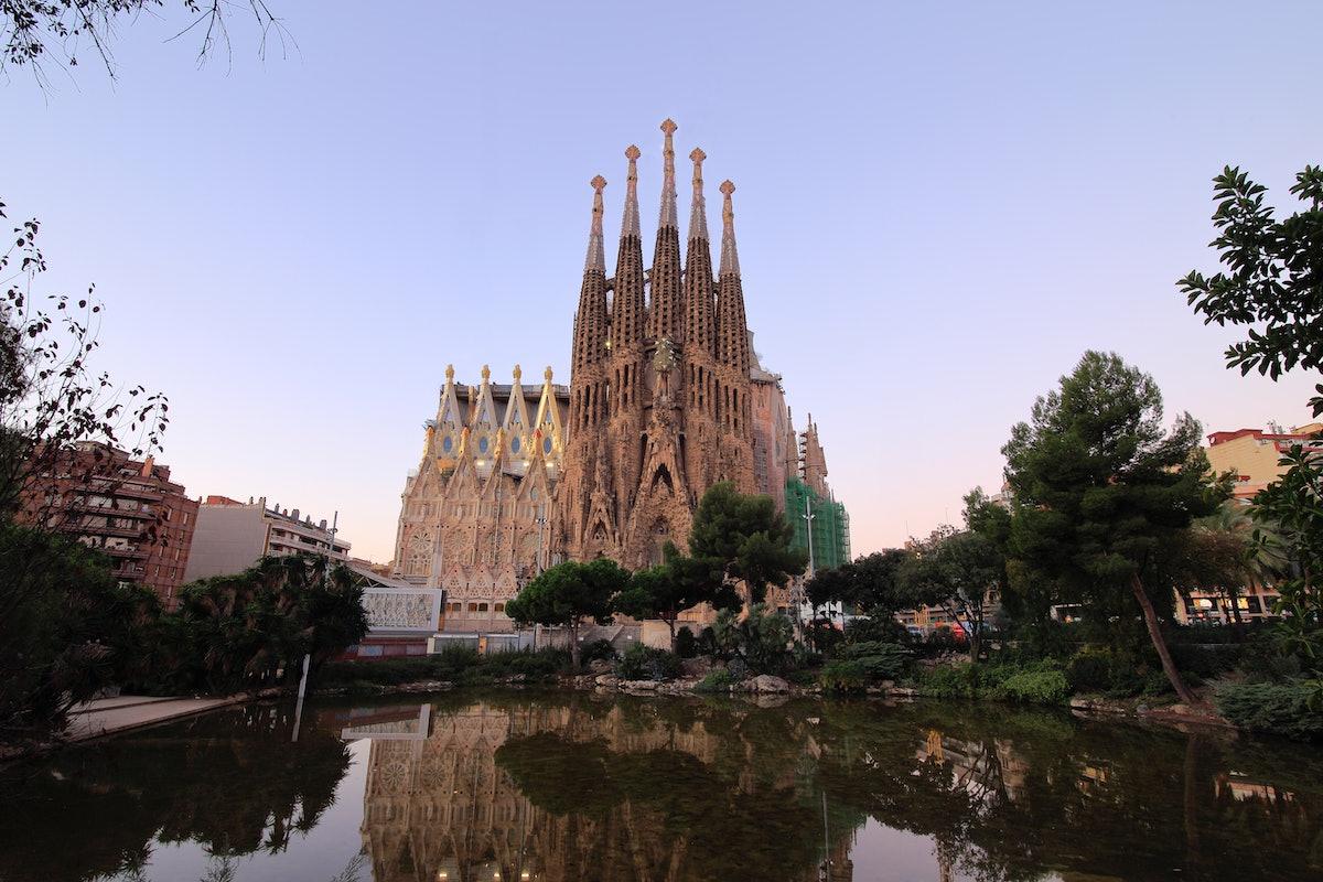 Basilica de la Sagrada Familia in Barcelona, Spain stands tall over a pond at sunset.
