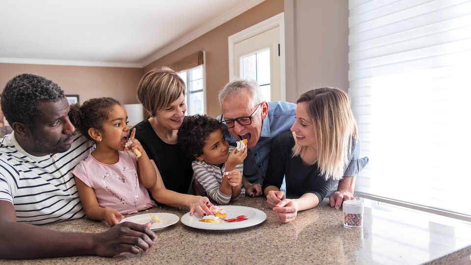 multicultural family sitting at kitchen island, little girl feeding grandpa dessert