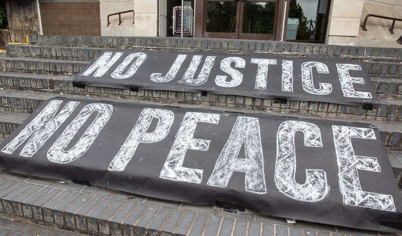 """Signs read """"No Justice, No Peace"""" at a Black Lives Matter march. Protesting can bring up old traumas and emotions, and tending to yourself beforehand is important, experts say."""