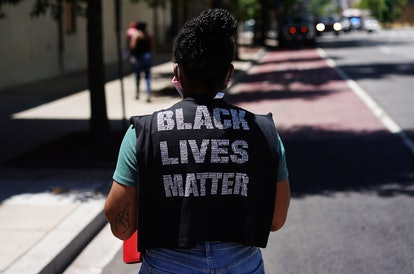 A woman wears a Black Lives Matter shirt. Self-care before protests can involve meditation, rituals, and other calming methods.
