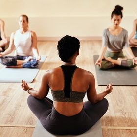 A black person leads a small yoga class. Anti-racism in fitness spaces is about more than hashtags.