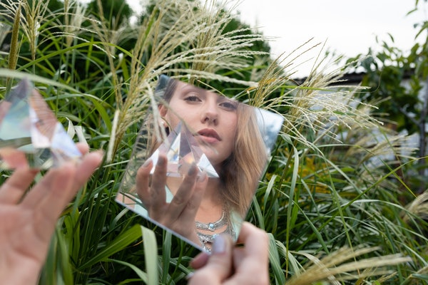 A young woman holds a glass prism and poses in a small mirror while sitting in a grassy field in the summer.