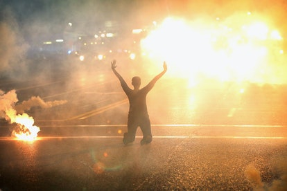 Tear gas reigns down on a woman kneeling in the street with her hands in the air after a demonstrati...