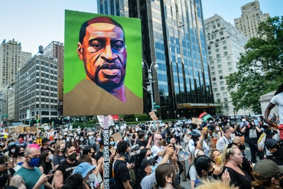 A painted portrait of George Floyd is held aloft at a protest. How To Handle Emotional Burnout As You Keep Pushing For Anti-Racist Change