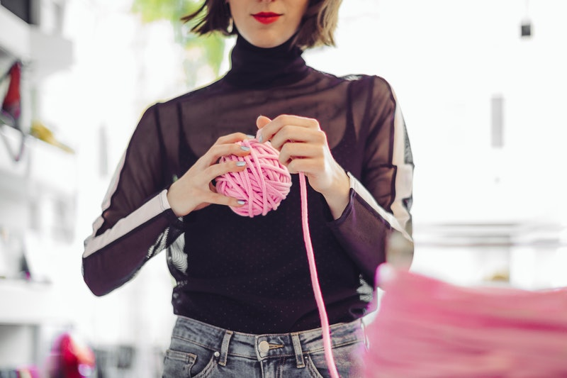 A woman knits from a big pink ball of yarn. People Are Making Instagram Accounts To Show Off Their New Quarantine Skills