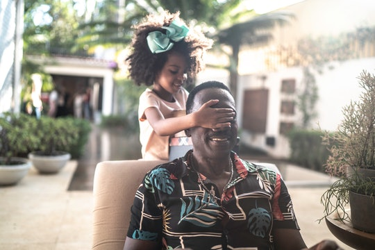 little black girl covering dad's smiling face