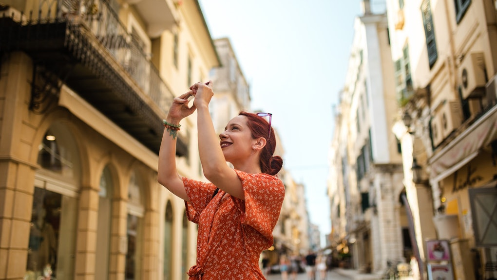 A young woman in a red dress takes a picture on her phone while vacationing in Greece.