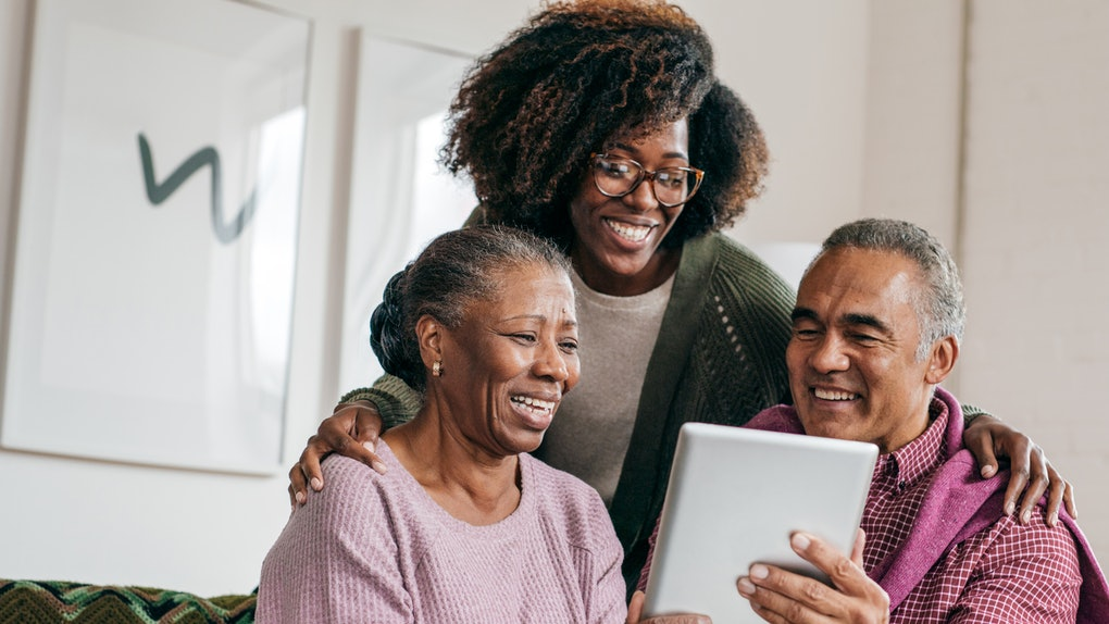 A young Black woman stands with her parents and laughs while they look at a tablet.
