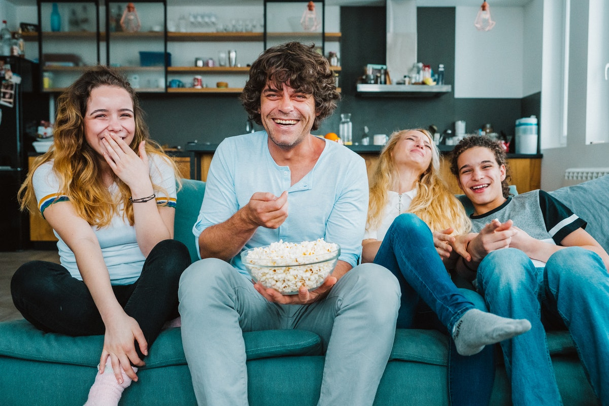 A group of siblings laughs with their dad while sitting on their couch and eating popcorn.