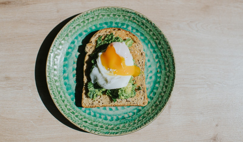 An avocado toast with an egg on it. The Gen Z Vs. Millennials Viral Beef Explained By Gen Z-Millennial Cusps