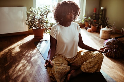 A woman meditates in a sun-dappled room. The Fitness Industry Needs To Confront Its Structural Racism, pros say.