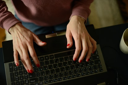 A woman types on a laptop as she contemplates her anxiety about going back to work after coronavirus.