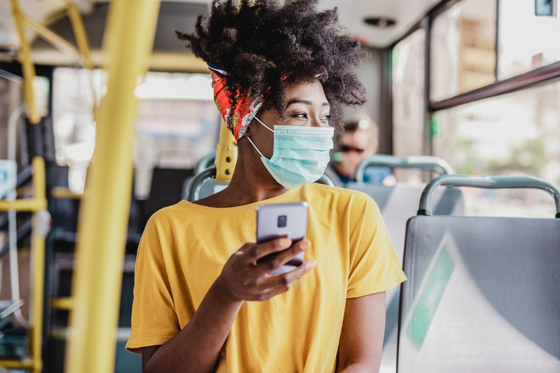 A woman looks out the window of a bus wearing a face mask. How To Handle Anxiety About Going Back To Work, According To Experts