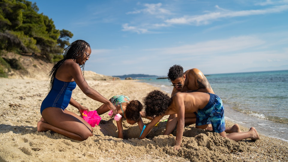 family playing in sand at beach