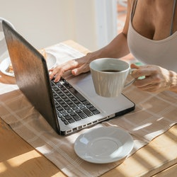 A woman deletes old facebook posts while drinking a coffee