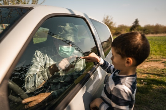boy and grandfather touching fingers through car window