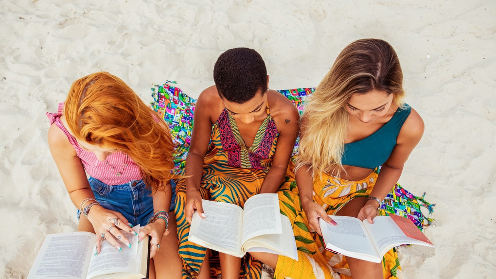 Three young women sit on the beach and read books in the middle of summer.