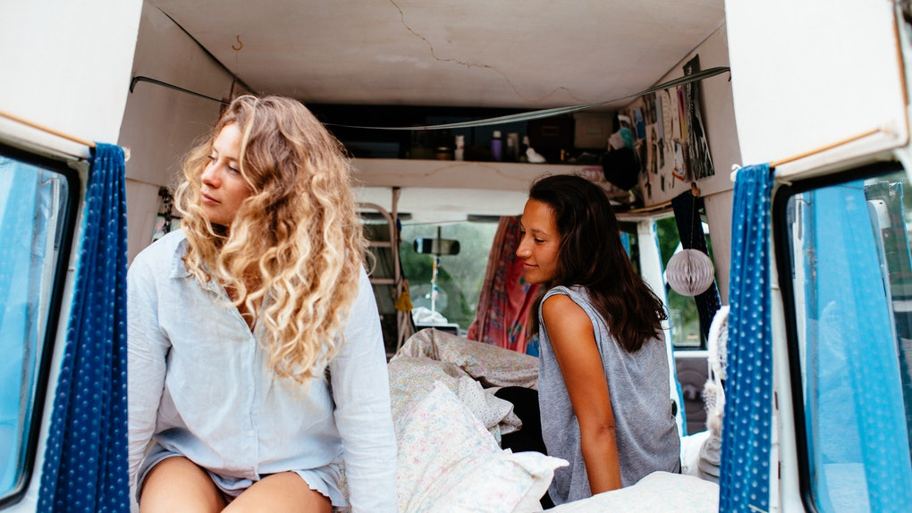 Two best friends sit in the back of a campervan that's decorated with pillows, pictures, curtains, and lanterns.