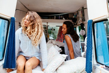 Two best friends sit in the back of a campervan that's decorated with pillows, pictures, curtains, a...