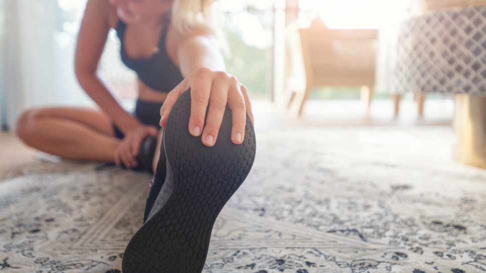 A person leans into a hamstring stretch at home. Stretching is especcially important when you're sitting all day.