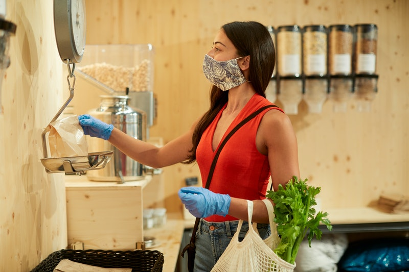 A woman wearing a face mask at the grocery store. Washing your cloth face mask after every use with ...