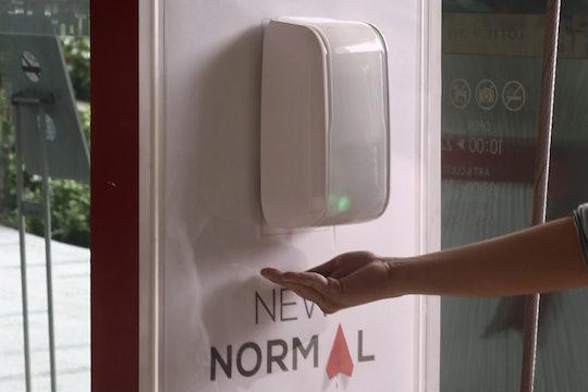 person holding hand under hand sanitizer dispenser